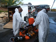 Allstate Animal Control technicians in hazmat suits performing skunk odor treatment